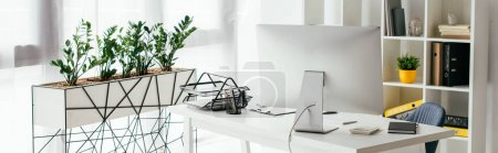 Foto de Panoramic shot of table with computer and document tray near bookcase and flowerpot with plants - Imagen libre de derechos