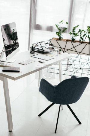 Foto de White table with computer, notebook, document tray, glass near office chair and flowerpot with plant - Imagen libre de derechos