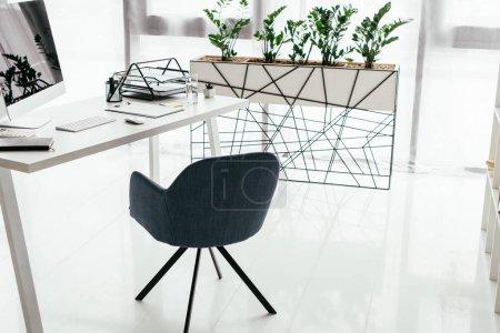 Photo pour Table blanche avec ordinateur, plateau de documents et ordinateur portable près de la chaise de bureau et pot de fleurs avec plante - image libre de droit
