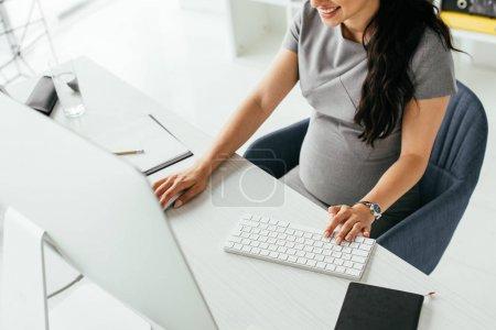 Photo pour Vue recadrée de femme enceinte s'asseyant derrière la table et travaillant sur l'ordinateur - image libre de droit