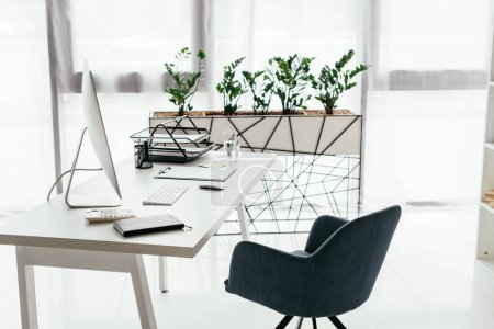 Photo for White table with computer, document tray, glass and notebook near office chair and flowerpot with plant - Royalty Free Image