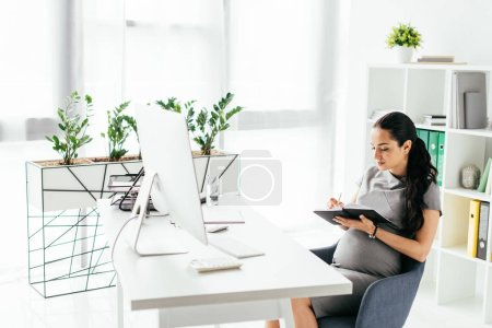Photo for Pregnant woman sitting in room with bookcase and flowerpot with plants behind table and taking notes in notebook - Royalty Free Image