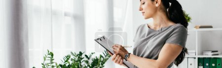Photo pour Panoramic shot of pregnant woman taking notes in notebook in office - image libre de droit