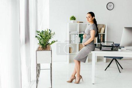 Photo pour Vue pleine longueur de femme enceinte restant dans le bureau avec le pot de fleur avec la plante, la table et la bibliothèque - image libre de droit