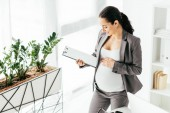 "Постер, картина, фотообои ""high angle view of pregnant woman looking at folder while standing in office near flowerpot with plant"""