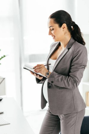 Photo for Pregnant woman taking notes while standing in office - Royalty Free Image
