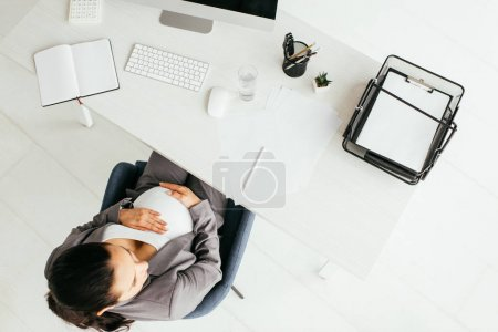 Photo for Top view of pregnant woman sitting behind table with computer, notebook, document tray, calculator, glass, keyboard, papers and pencil - Royalty Free Image