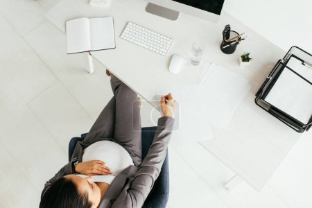 Photo for Top view of pregnant woman sitting behind table with computer, notebook, document tray, calculator, glass, keyboard, papers and pencil, and taking notes - Royalty Free Image