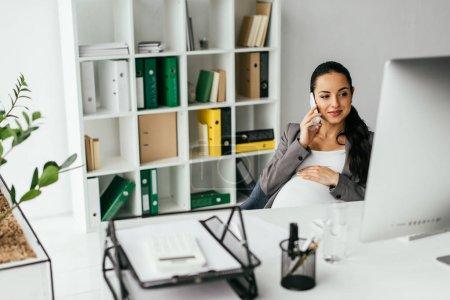 Photo pour Foyer sélectif de la femme s'asseyant derrière la table dans le bureau et parlant sur le smartphone - image libre de droit