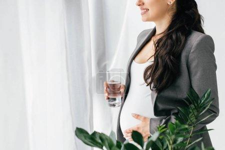 Photo pour Vue recadrée de la femme enceinte tenant le verre avec de l'eau tout en se tenant près de la fenêtre et la plante - image libre de droit