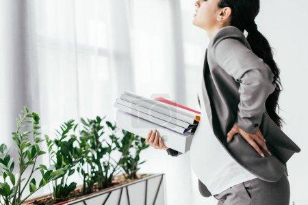 Foto de Pregnant woman holding back while standing with many folders - Imagen libre de derechos