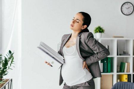 Photo pour Femme enceinte épuisée retenant et abondance de dossiers - image libre de droit