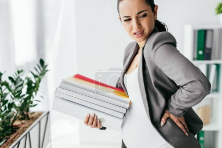 Schwangere erträgt Schmerzen und hält Ordner im Büro