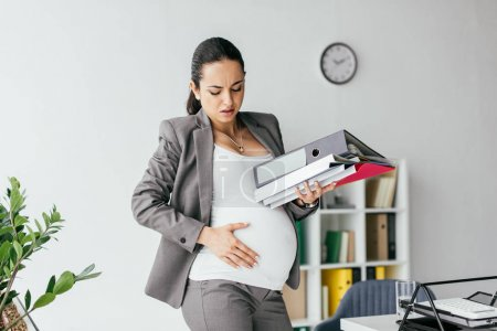 Photo for Pregnant woman holding belly, enduring pain and holding folders - Royalty Free Image