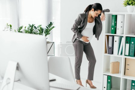 Photo for Pregnant woman standing near bookcase and leaning on it because of pain - Royalty Free Image