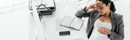 Photo pour Tir panoramique de la tête de fixation de femme enceinte avec la main et s'asseyant derrière la table avec l'ordinateur, le cahier et le plateau de document - image libre de droit