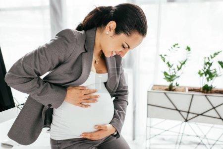 Photo pour Femme enceinte retenant le ventre et faisant la grimace en raison de la douleur tout en s'asseyant dans le bureau - image libre de droit