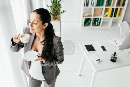 Photo for High angle view of pregnant woman standing in office and drinking coffee - Royalty Free Image