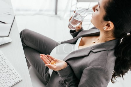 Photo for High angle view of pregnant woman drinking water and holding pills - Royalty Free Image