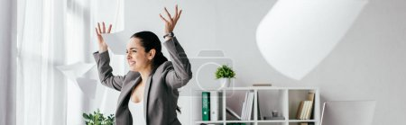 Photo for Panoramic shot of irritated pregnant woman throwing papers in air while standing near table in office - Royalty Free Image
