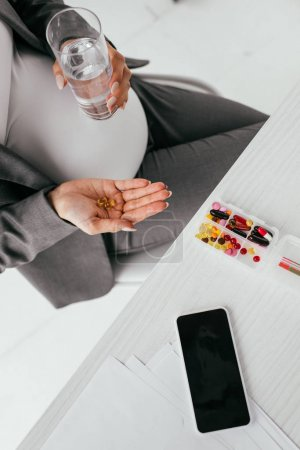 Photo pour Vue supérieure de la femme enceinte retenant des pillules tout en s'asseyant derrière la table avec la boîte de pillule - image libre de droit