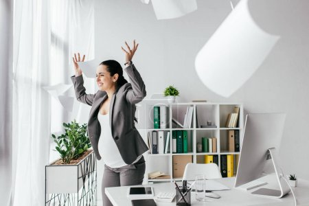 Photo for Irritated pregnant woman throwing papers in air while standing near table in office - Royalty Free Image