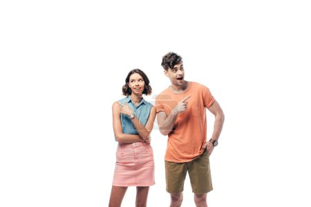 Foto de Young, smiling man and woman looking away and pointing with fingers isolated on white - Imagen libre de derechos