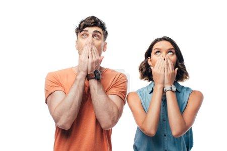 choqué homme et femme regardant vers le haut et couvrant les visages avec les mains isolées sur blanc