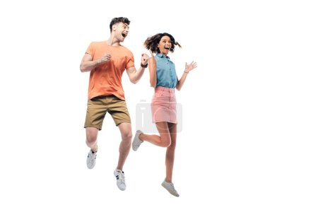 Foto de Happy man and woman jumping and looking away while showing yes gesture isolated on white - Imagen libre de derechos