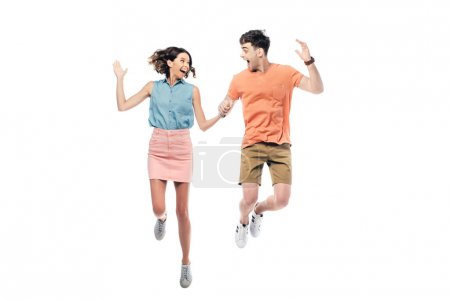 Photo for Excited man and woman jumping while looking at each other isolated on white - Royalty Free Image