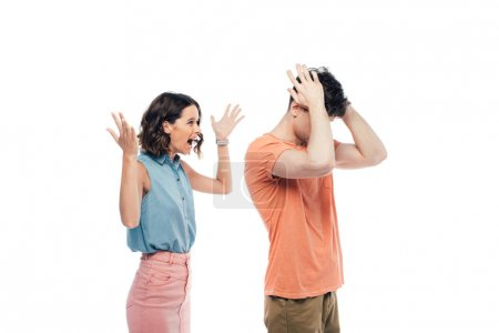 Foto de Angry young woman gesturing while quarreling at offended boyfriend isolated on white - Imagen libre de derechos