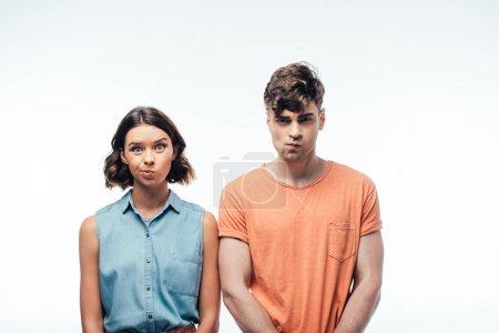 Photo pour Jeune homme et femme mécontents regardant l'appareil-photo et grimaçant sur le fond blanc - image libre de droit