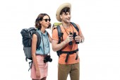 two young tourists with binoculars and digital camera looking away and smiling isolated on white