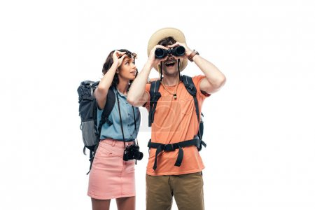 excited tourist looking in binoculars near cheerful young woman isolated on white