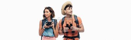 Photo pour Photo panoramique de deux touristes souriants avec l'appareil-photo numérique et les jumelles regardant loin isolés sur le blanc - image libre de droit