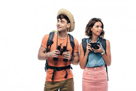 Photo pour Two cheerful young tourists with binoculars and digital camera looking away isolated on white - image libre de droit