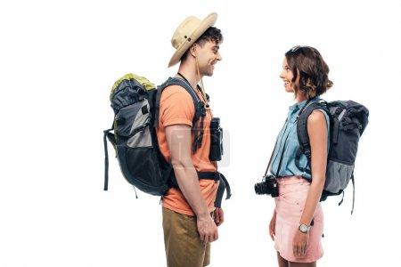 Photo pour Deux jeunes touristes souriants avec des sacs à dos regardant l'un l'autre isolés sur le blanc - image libre de droit