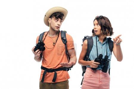 Photo pour Jeune femme pointant avec le doigt tout en regardant l'homme pensif retenant l'appareil-photo numérique d'isolement sur le blanc - image libre de droit