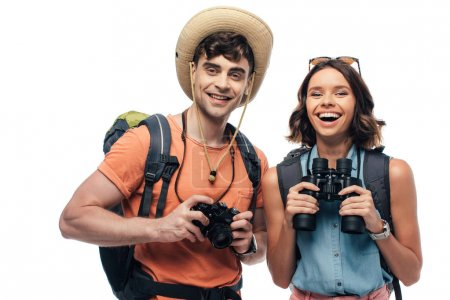 two happy young tourists with digital camera and binoculars smiling at camera isolated on white