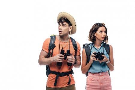 Photo pour Deux jeunes touristes réfléchis avec l'appareil photo numérique et les jumelles regardant loin isolés sur le blanc - image libre de droit