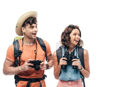 two excited young tourists with digital camera and binoculars looking away isolated on white