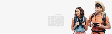 Photo pour Photo panoramique de deux jeunes touristes souriant tout en regardant loin isolé sur le fond gris - image libre de droit