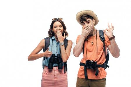 Photo pour Deux touristes gais affichant le pouce vers le haut et le signe ok tout en regardant l'appareil-photo isolé sur le blanc - image libre de droit
