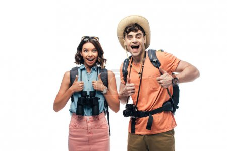 Foto de Two excited tourists showing thumbs up while looking at camera isolated on white - Imagen libre de derechos