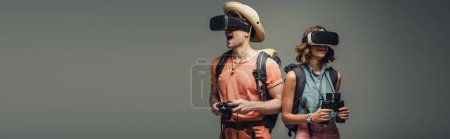 Photo for Panoramic shot of two young tourists using virtual reality headsets on grey background - Royalty Free Image