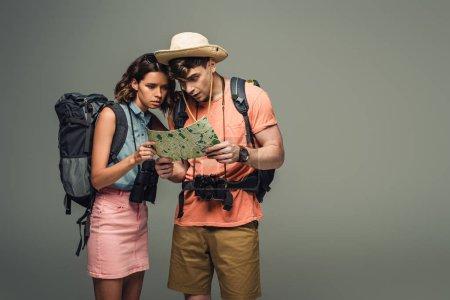 Photo pour Deux jeunes touristes regardant la carte géographique sur le fond gris - image libre de droit