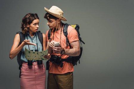 Foto de Two young tourists talking while holding geographic map on grey background - Imagen libre de derechos