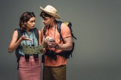 """Постер, картина, фотообои """"two young tourists talking while holding geographic map on grey background"""""""