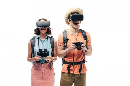 Photo pour Deux touristes gais avec des jumelles et un appareil photo numérique à l'aide de casques de réalité virtuelle isolés sur le blanc - image libre de droit