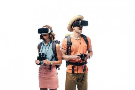 Photo pour Deux jeunes touristes avec des jumelles et un appareil photo numérique utilisant des casques de réalité virtuelle isolés sur le blanc - image libre de droit